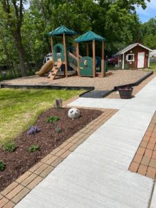 Photograph of the backyard at The Children's Center of Medina County shows brick pavers lining both sides of the sidewalk. There is a landscaped garden with newly planted flowers along the pavers on the left. In the background, there is a playground and a gingerbread-style playhouse.